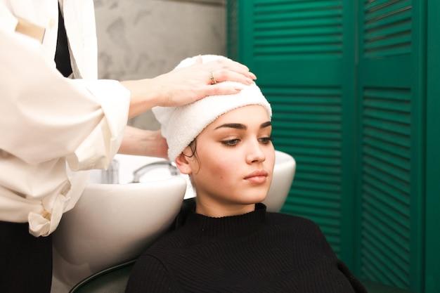 Fryzjer zawija włosy klienta w ręcznik po umyciu głowy
