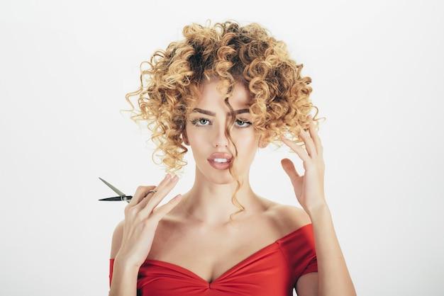 Fryzjer zmysłowa dziewczyna z kręconymi włosami trzyma nożyczki fryzjerskie fryzjer narzędzie makijaż i