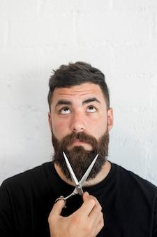Fryzjera męskiego mienia fachowi nożyce zbliżają brodę przy zakładem fryzjerskim