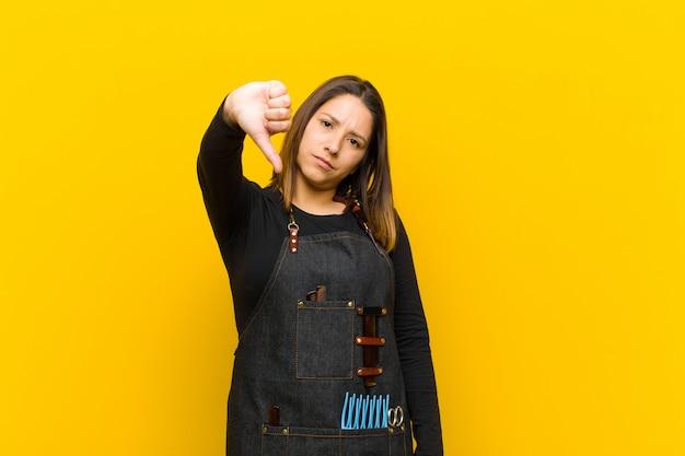 Fryzjerka czuje się krzyżowo, zła, zirytowana, rozczarowana lub niezadowolona, pokazuje kciuk w dół z poważnym spojrzeniem na pomarańczę