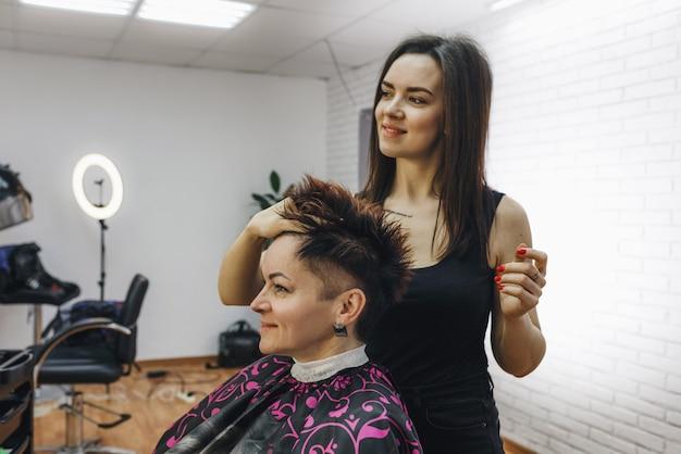 Fryzjerka dziewczyna robi fryzurę dla klientki w nowoczesnym salonie kosmetycznym. sztuka fryzjerska.