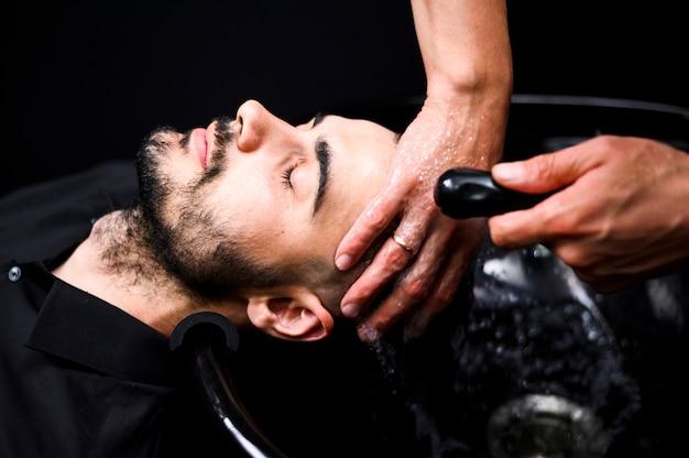 Fryzjerka myjąca włosy klienta w salonie
