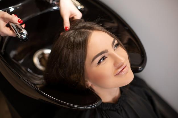 Fryzjerka myje włosy swoich klientów