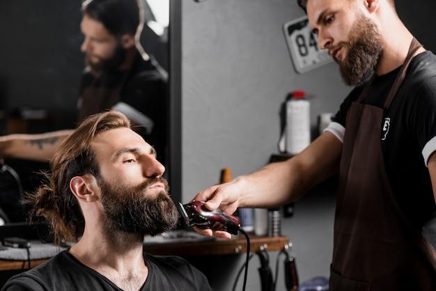 Fryzjerka przycina włosy męskiego klienta za pomocą elektrycznej trymera