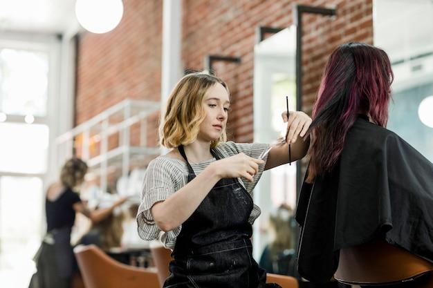 Fryzjerka przycinająca włosy klienta w salonie kosmetycznym
