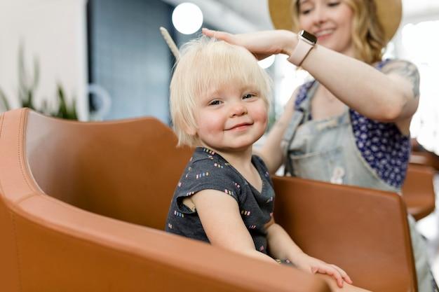 Fryzjerka robi fryzurę uroczemu blondynowi