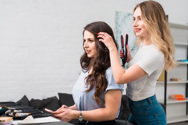 Fryzjerka robi loki dla młodej kobiety