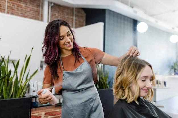 Fryzjerka rozpylająca myszkę na włosach klienta
