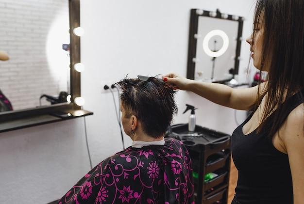 Fryzjerka starannie ułoży fryzurę dla swojej klientki w salonie kosmetycznym