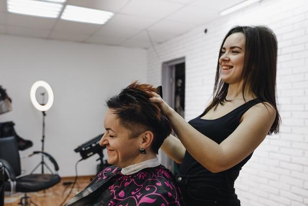 Fryzjerka układa włosy dla klientki w nowoczesnym salonie kosmetycznym i wesoło się śmieje