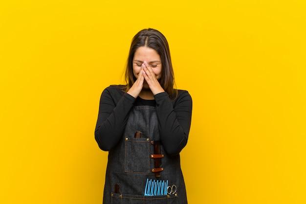 Fryzjerka wyglądająca na szczęśliwą, wesołą, szczęśliwą i zaskoczoną zakrywającą usta obiema rękami pomarańczowymi