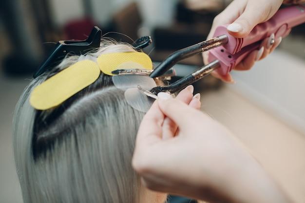 Fryzjerka wykonująca przedłużanie włosów do młodej kobiety o blond włosach w profesjonalnym przedłużaniu włosów w salonie kosmetycznym