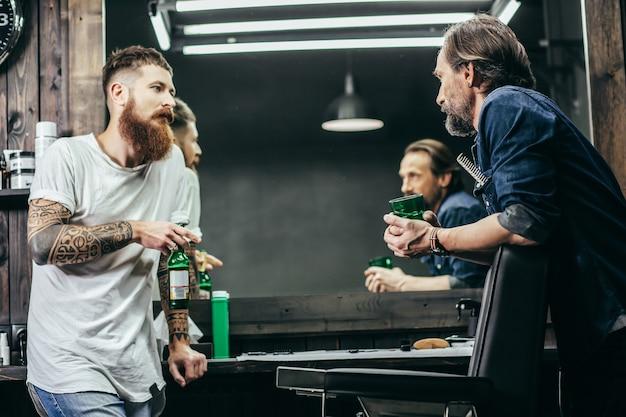 Fryzjerzy stojący naprzeciwko siebie i rozmawiający przy piwie