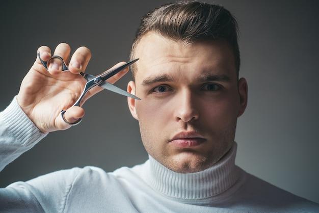 Fryzura błyszcząca fryzjer trzyma stalowe nożyczki. stwórz swój styl. macho pewny siebie fryzjer strzyżony. koncepcja usługi fryzjera. profesjonalny sprzęt fryzjerski. ścinać włosy. człowiek ścisłej twarzy trzymać nożyczki.