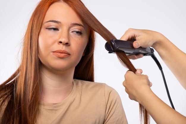Fryzura dla rudowłosej kobiety używającej prostownicy do włosów, patrząc z boku na usługi kosmetyczne