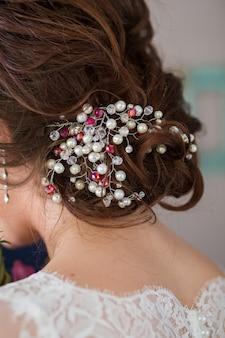 Fryzura ślubna panny młodej, piękne ozdoby w głowie. akcesoria ślubne. biżuteria damska dla dziewczynek. szczegóły dotyczące małżeństwa i pary małżeńskiej
