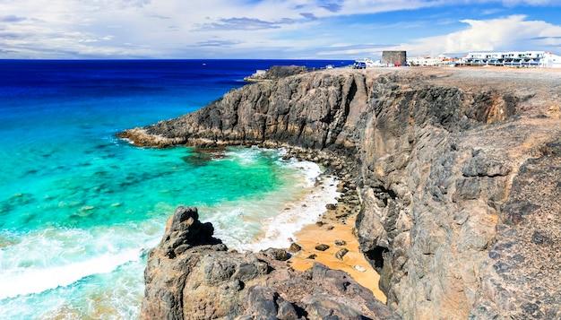 Fuerteventura - widok na skalistą plażę i wieżę toston w el cotillo. wyspy kanaryjskie