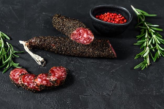 Fuet, salami i gałązka rozmarynu. tradycyjna hiszpańska kiełbasa. czarne tło. widok z góry. miejsce na tekst