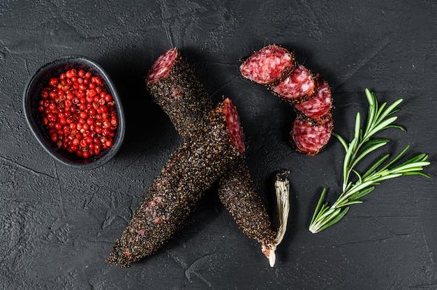 Fuet, salami i gałązka rozmarynu. tradycyjna hiszpańska kiełbasa. czarne tło. widok z góry