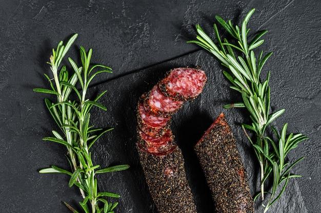 Fuet, salami i gałązka rozmarynu. tradycyjna hiszpańska kiełbasa.