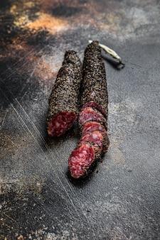 Fuet, salami. tradycyjna hiszpańska kiełbasa. czarne tło. widok z góry
