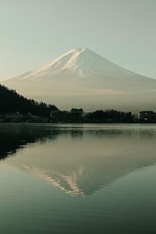 Fuji widok górski i kawaguchiko jezioro w ranku wschodzie słońca, zima sezony przy yamanachi, japonia. krajobraz z linii horyzontu odbiciem na wodzie.