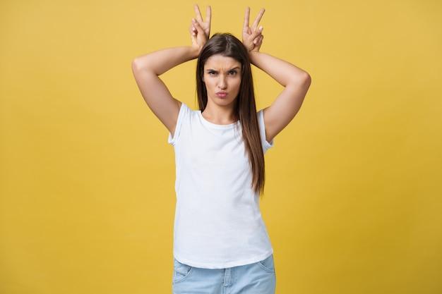 Fun and people concept - headshot portret szczęśliwej kobiety rasy kaukaskiej z piegami uśmiecha się i pokazuje uszy królika palcami nad głową. pastelowe żółte tło studyjne. kopiuj miejsce.