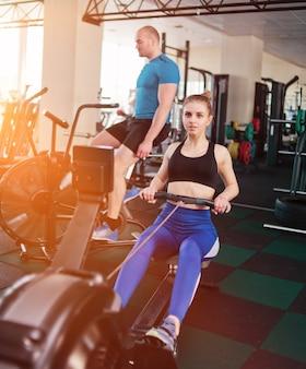 Funkcjonalna koncepcja treningu. sport mężczyzna i kobieta robi ćwiczenia w wioślarstwie symulatora i rowerze powietrznym na siłowni