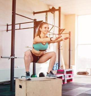 Funkcjonalny nowoczesny trening. młoda blond kobieta skacze w kucki na wysokim drewnianym pudełku.