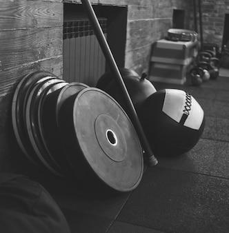 Funkcjonalny Sprzęt Treningowy. Piłka Lekarska, Sztanga, Kij Gimnastyczny Na Tle Drewnianej ściany W Ciemnej Sali Gimnastycznej Premium Zdjęcia