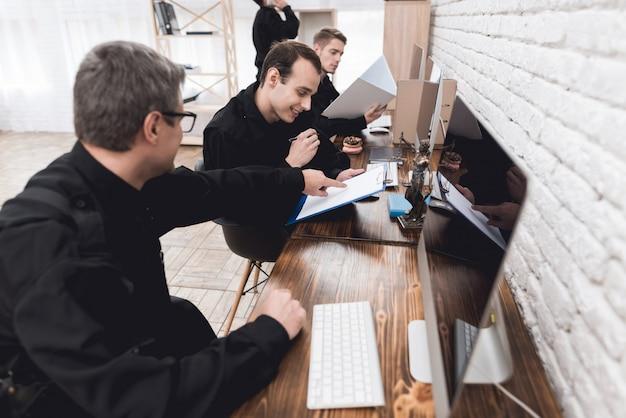Funkcjonariusze policji pracują przy komputerze na posterunku policji.