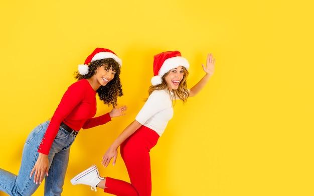 Funny christmas banner z widokiem z boku dwóch mieszanych rasy uśmiechnięte kobiety na jednej nodze w pozycji biegacza w czapce świętego mikołaja