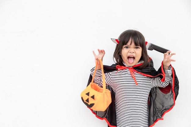 Funny halloween kid concept, mała urocza dziewczyna z kostiumem halloweenowym duchem przerażającym trzyma pomarańczowego dyniowego ducha pod ręką, na białym tle