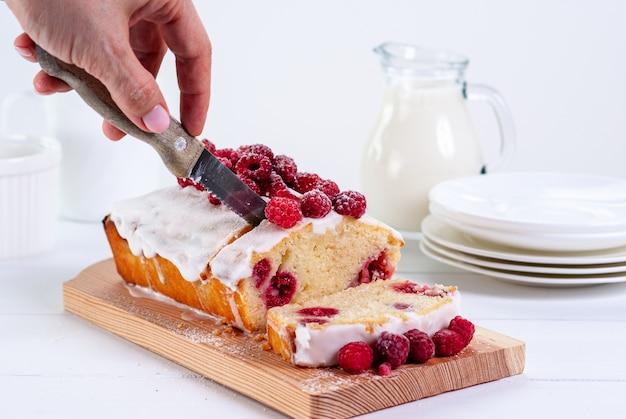 Funt jogurtowy z malinami i polewą cukrową na białym tle