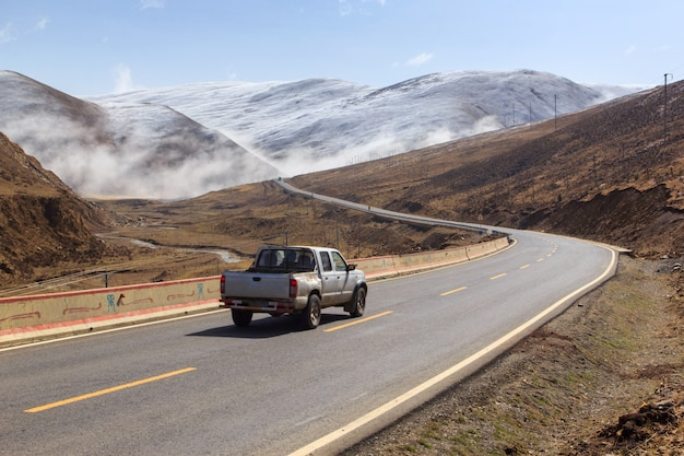 Furgonetka na drodze, piękna zimy droga w tybet pod śnieżną górą sichuan chiny