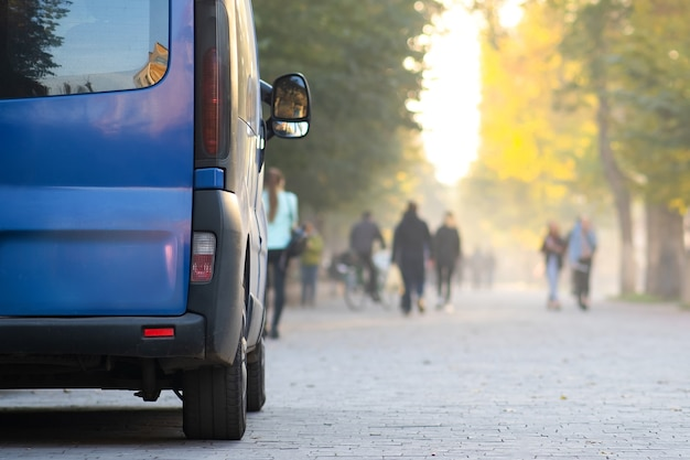 Furgonetka pasażerska zaparkowana na poboczu alei miasta z niewyraźnymi pieszymi jesienią.