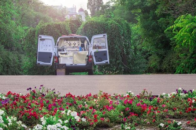 Furgonetka z kawą i ciężarówka z napojami w zielonym ogrodzie
