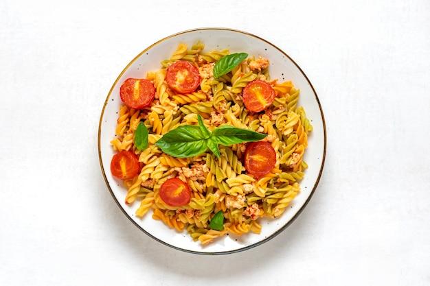 Fusilli - klasyczny włoski makaron z pszenicy durum z mięsem kurczaka, pomidorami cherry, bazylią w sosie pomidorowym w białej misce na białym drewnianym stole kuchnia śródziemnomorska widok z góry flat lay.