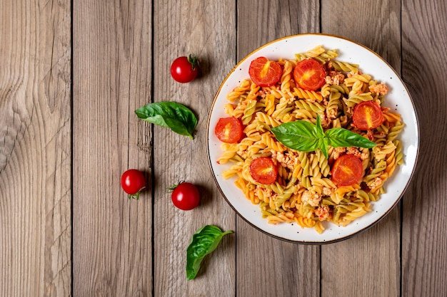 Fusilli - klasyczny włoski makaron z pszenicy durum z mięsem kurczaka, pomidorami cherry, bazylią w sosie pomidorowym w białej misce na drewnianym stole kuchnia śródziemnomorska widok z góry flat lay.