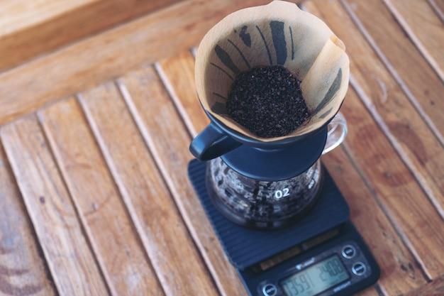 Fusy z kawy w papierowym filtrze na cyfrowej wadze kawy podczas robienia kroplówki kawy na vintage drewnianym stole