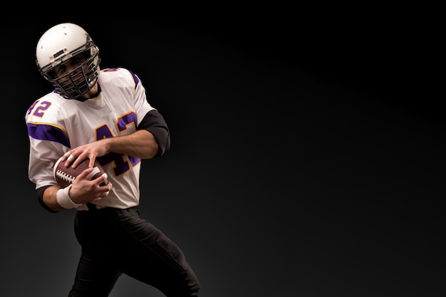 Futbol amerykański gracz trzyma piłkę w jego rękach