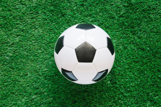 Futbolowy tło na trawie z piłką