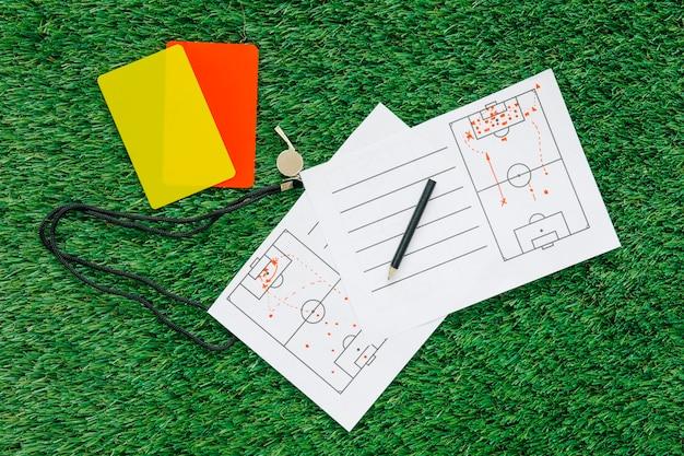 Futbolowy tło na trawie z taktyka papierem i kartami