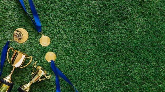 Futbolowy tło z medalami i trofeum obok copyspace