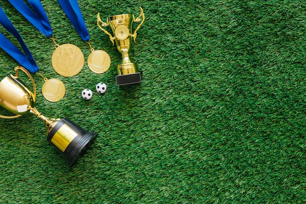 Futbolowy tło z medalami i trofeum