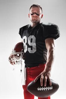 Futbolu amerykańskiego gracz pozuje z piłką na bielu