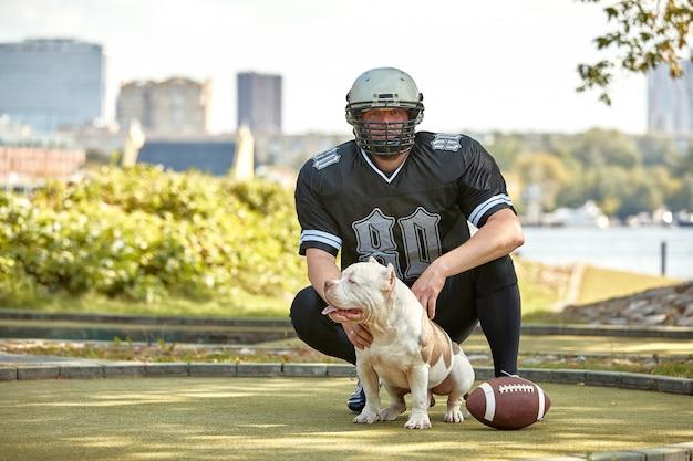 Futbolu amerykańskiego gracz z psem pozuje na kamerze w parku. copyspace, banner sportowy. futbol amerykański, sport dla ochrony zwierząt.