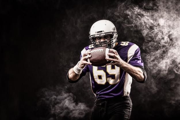 Futbolu amerykańskiego gracza mienia piłka w jego rękach w dymu
