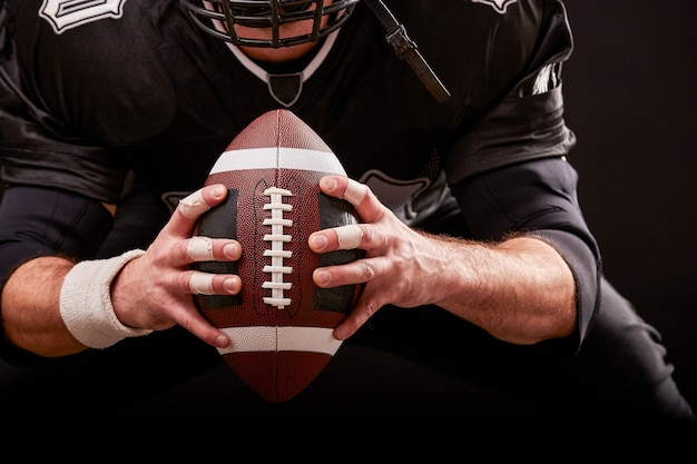 Futbolu amerykańskiego sportowa gracz na stadium z światłami na czarnym tle.