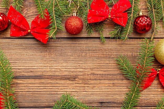 Futro świerk sosna iglaste gałęzie łuki błyszczące błyszczące kolorowe czerwone złote zabawki kulki pudełko pudełko łuk na brązowym szczotkowanym drewnianym tle